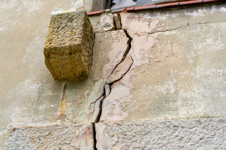Broken wall with cracks close-up. Destruction of the house Stock fotó