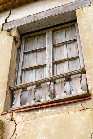 Old broken window of an abandoned house with wooden shutters. Cracked destroyed wall. Gloomy view Stock fotó