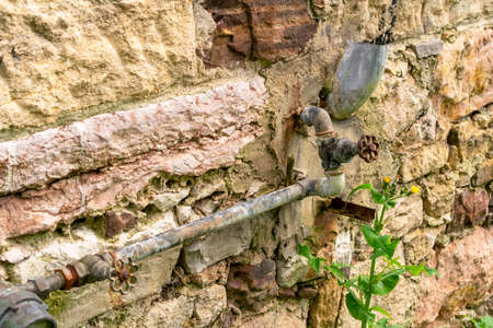 Old rusty water valve with pipes on the background of a destroyed stone wall of an abandoned house