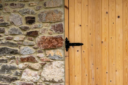 Black hinge of new wooden plank gate. Stone wall. Copy space Stock fotó