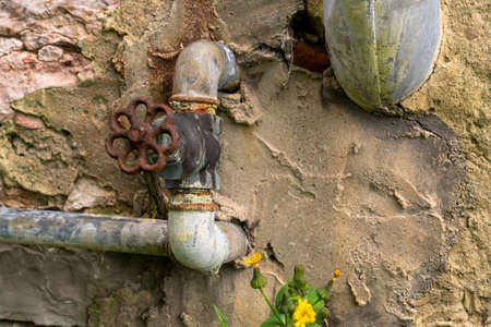 Old abandoned valve with pipe on a stone wall close up