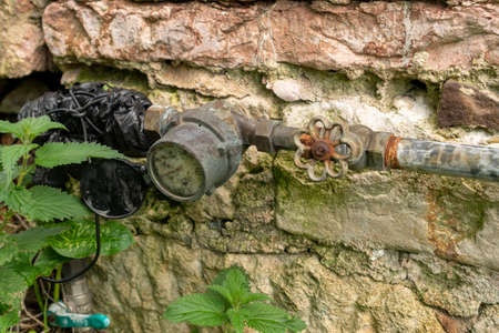 Antique stone wall texture background with water meter close up and grass Stock fotó