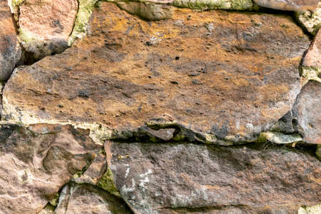 Ancient damaged rock wall of an abandoned house closeup for abstract background