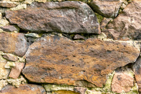 Textured natural stones close up in an old stone wall