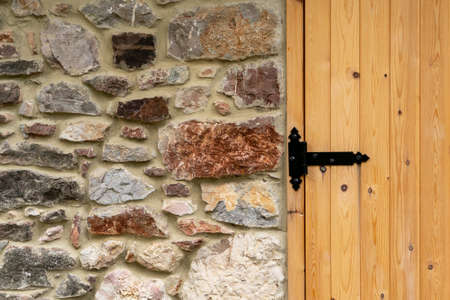 black hinge of the wooden plank gate of the stone barn. Copy space