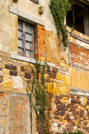 Old window with wooden shutters on a cracked stone and brick wall with ivy. Abandoned ancient house Stock fotó