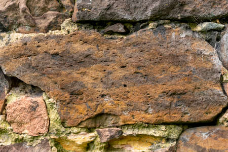 Stone brown wall made of natural weathered stones close-up Stock fotó