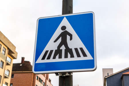 Pedestrian crossing road sign on the street close-up on a metal pillar fastened against the background of buildings and the sky. Road safety concept Stock fotó