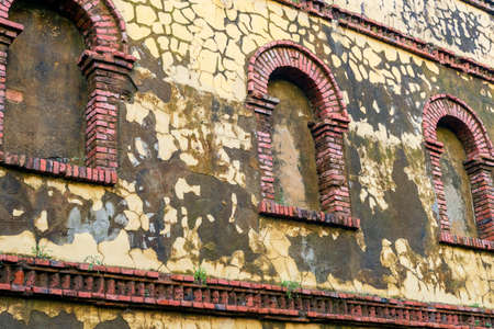 Old brick walled up arched windows on a cracked mossy yellow wall. Antique ancient building