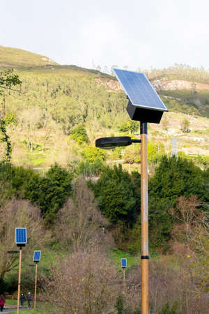 Alley with Photovoltaic street lighting poles in a hilly park. Alternative energy technology concept Stock fotó