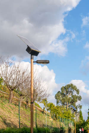 Park Alley with photovoltaic street lighting poles in a hilly park. Alternative solar energy technology concept Stock fotó