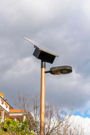 Street lamp with photovoltaic panel close-up for receiving solar energy against the background of a cloudy sky and a cottage on a hill