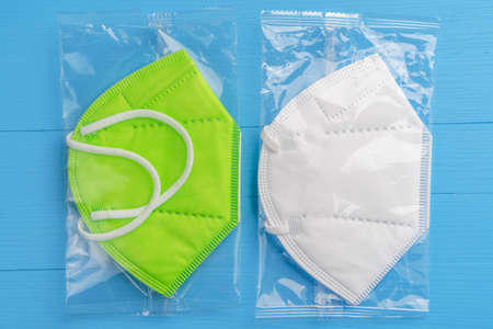 KN95 green and white protective respiratory masks in shiny cellophane bags on a blue board close up. Health care concept Stock fotó