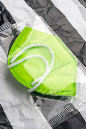 KN95 professional protective respiratory mask in transparent packaging on abstract striped wrinkled paper Stock fotó