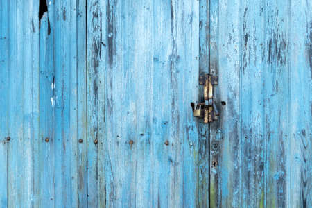 Plank old blue weathered gate with a keyhole and a padlock with rusted iron. Copspace