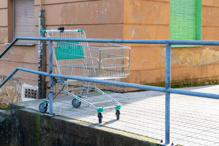 Abandoned empty grocery cart in an old street courtyard with shabby walls and closed shutters. Discarded shopping cart chained to the handrails of a concrete staircase Stock fotó