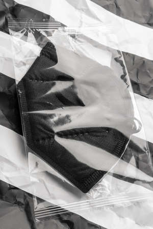 Pack with black respiratory medical mask on striped black white background. Close up. KN95