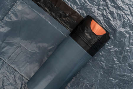 Black bin bags on a roll. Crumpled wrinkled abstract background. Orange strap