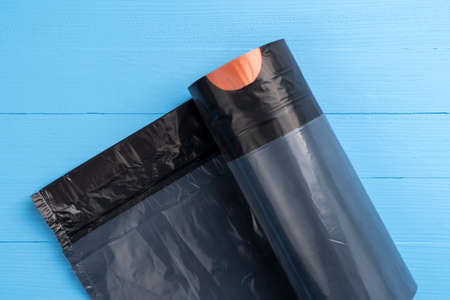 Black garbage bags on a roll. Wooden blue background. Orange strap closure Stock fotó