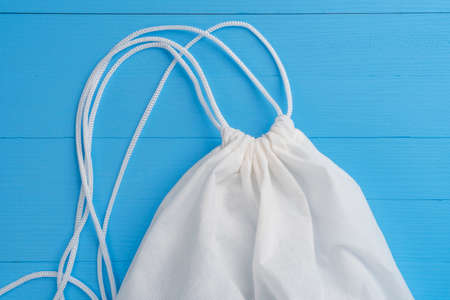 Knotted Rope Tied Closed Synthetic Textile Bag Close Up On Wooden Plank Blue Background. Delivery Concept Фото со стока
