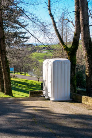 Dry closets in a public autumn park. White plastic modules of mobile toilet WC close up