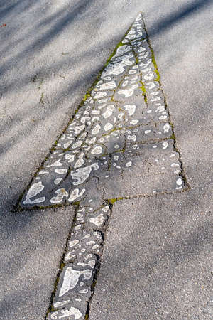 Road markings arrow with cracked peeled white paint on an old road with cracks and overgrown grass in the shade of trees Stock fotó