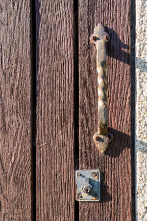Old plank door with an ancient rusty iron ornamental handle and a peeling keyhole. Rusty screws. Vintage concept