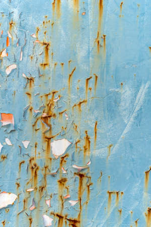 Rusty peeled metal wall painted blue with rust and paint stains. Abstract textured background