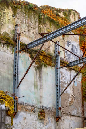 Steel beams supporting an old mossy wall of a destroyed building Stock fotó