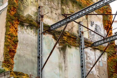 Steel beams supporting an old mossy wall of a destroyed building Фото со стока