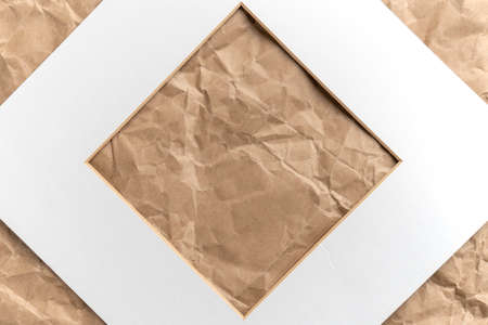 Paper white square cardboard frame on crumpled brown kraft paper. Abstract background. Copy space Фото со стока