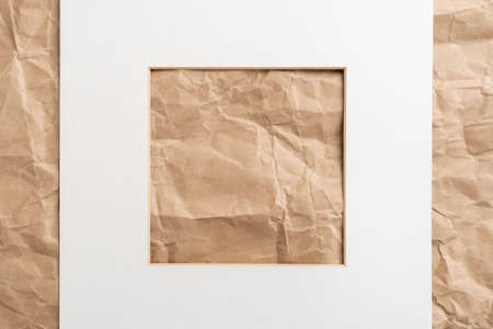 White paper picture frame on a crumpled wrinkled packaging wrapping background. Copy space