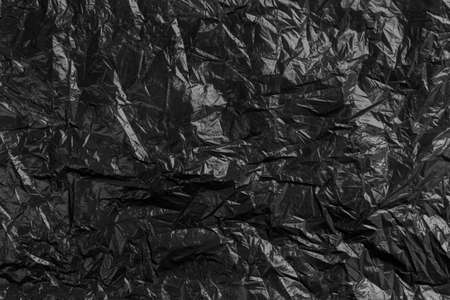 Plastic black crumpled disposable trash bag. Abstract recycled background