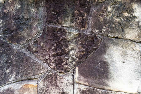 Old rotten stone wall with weathered seams. Abstract texture