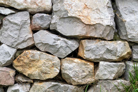 Stone wall with stacked natural stones close-up. Natural rock background