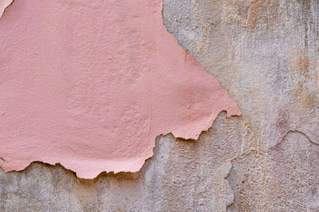 Peeling dried pink paint on a cement concrete old wall. Grunge vintage concept