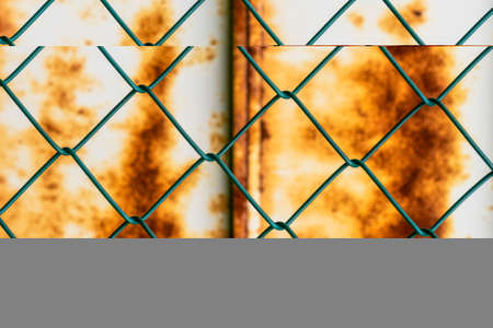 Mesh pattern on the background of a rusty iron wall. Green chain-link fence and corrosive sheet metal