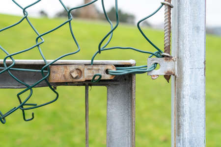 Mesh chain link fence fastening close-up. Torn fencing cells are fixed with a metal plate