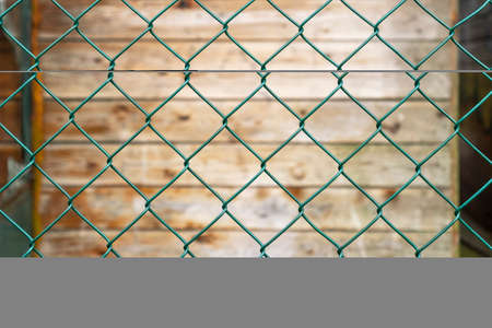 Steel green fence mesh netting and old plank wooden wall in blur on the background. Abstract background. Security concept. Square cells close up