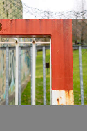 Old rusty football goal on an abandoned sports ground with blurred graffiti and mesh fence. Red white corner close up