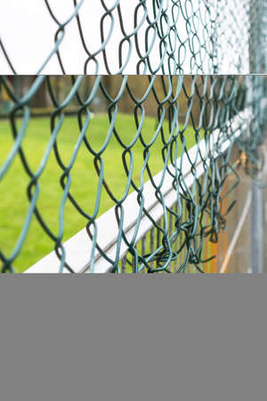 Mesh chain link fence with braided metal green cells close up
