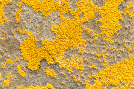 Old wall with yellow peeled weathered paint. Abstract textured background Фото со стока