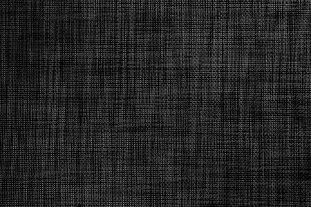 Textured gray black surface of woven plastic material. Abstract dark background