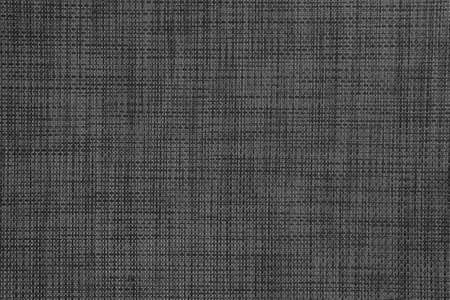 Textured plastic wicker surface with an abstract pattern. Dark background