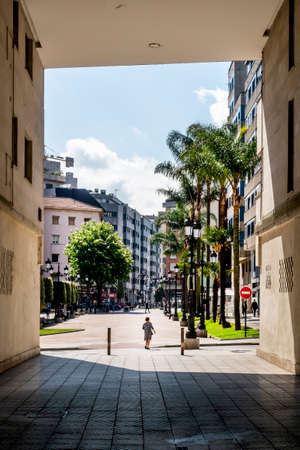 Oviedo, Spain - April 20, 2021: Lame disabled woman comes out of a dark courtyard onto a bright palm summer alley on a modern European city street. Dramatic view. Road sign NO ENTRY. Social contrast concept. Loneliness idea