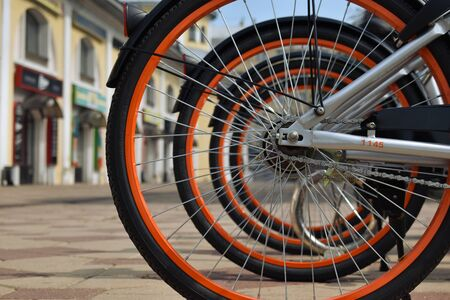Bicycle rear wheels on blurry background with orange rims. Reklamní fotografie