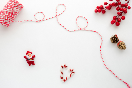 Christmas composition. Christmas Ribbon, holly berry, candy cane, santa claus, and pine cone. Creative flat lay, top view design