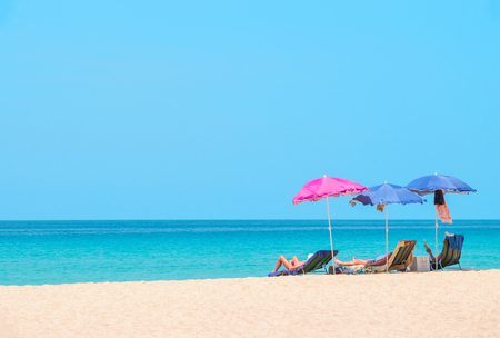 People sunbathing and relaxing on beach chairs. Sea view and blue sky. Summer background -  Image  Banque d'images