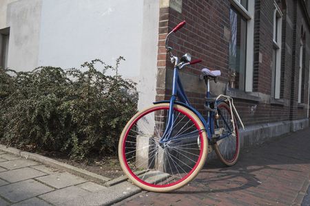 blue bicycle next to a wall of ghost house with white and red tires