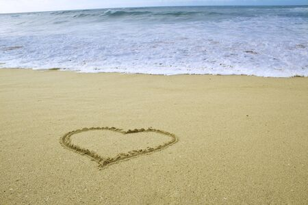 photo of simply heart shape drawn on sand on the beach by the ocean
